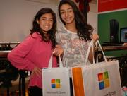 Customers pose with gift bags at the November grand opening of the 14th Microsoft Store at Tysons Corner Center in McLean, Va. One of those stores will open soon at Oak Park Mall in Overland Park.