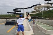 A Schlitterbahn lifeguard signals that the slide is clear as an attendee exits the new attraction.