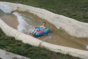 A girl rides down the new King Kaw Rapids River attraction in her tube.