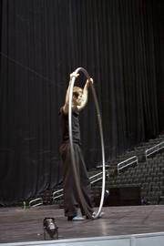 A Cirque du Soleil performer uses a large metal hoop to twist, turn and perform gravity-defying somersaults and acrobatics.