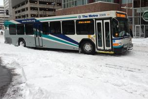 A bus makes its way through snow-packed roads near 10th and Main St. in downtown Kansas City.