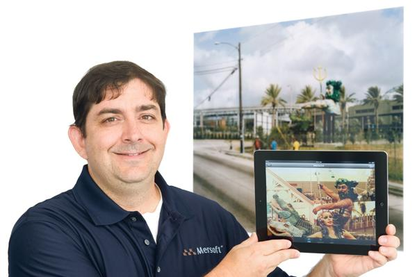 "Jeff Smith, CTO of Mersoft Corp., holds an iPad with an app that uses ""augmented reality"" technology to show a photograph of a sculpture from the 1984 World's Fair in New Orleans, in front of a photo of the same site today at a temporary exhibit at the Nelson-Atkins Museum of Art."