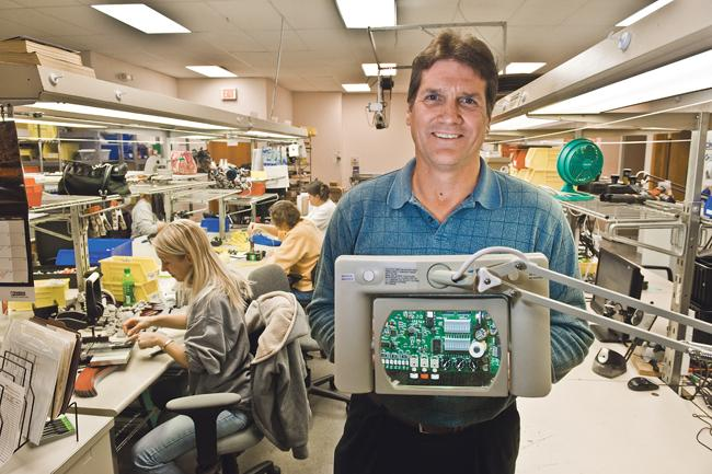 Denis Caye, president of Automated Motion Inc., holds a circuit board guidance control for an irrigation system that is manufactured at the company's Lee's Summit location.
