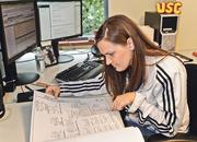 Ellen Foster, an architect with BRR Architecture, looks over a schematic of a project that she is working on.
