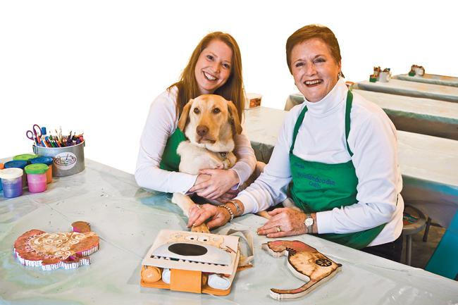 Katie Weiford and her mother, Sheila, are co-owners of Kookiedoodle Crafts LLC. With them is Katie's yellow Labrador, Saumus, one of three dogs at the walk-in arts-and-crafts studio for children ages 3-12.
