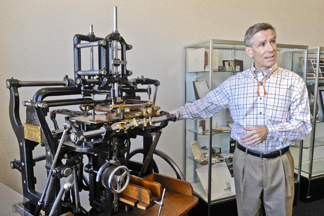 """Tension Corp. COO Bob Broadbear stands by an antique """"plunger machine"""" that the company used to fold envelopes from paper stock more than a century ago."""