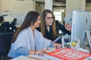 DMH employees Cailin Workman (left) and Ruth Stark collaborate on a project.