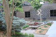 Mature trees, evergreens and  colorful annuals create a quiet spot in the middle of a busy medical establishment at North Kansas City Hospital. The Gift of Life Garden is a draw to patients, their loved ones and hospital employees.