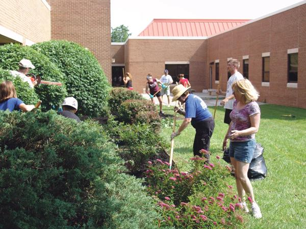 JE Dunn Construction employees and their families dig in to help refresh the grounds at Marillac in Overland Park during the United Way Day of Caring.