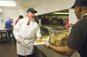 Sean O'Byrne, a vice president at the Downtown Council of Kansas City, passes a plate to fellow volunteer Gregory Hill while they serve lunch to those in need at the community kitchen at 750 Paseo Blvd. The Downtown Council helped move the kitchen closer to homeless shelters.