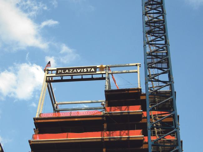 Work continues on the former West Edge project, now called Plaza Vista, as the project owners argue about its valuation.