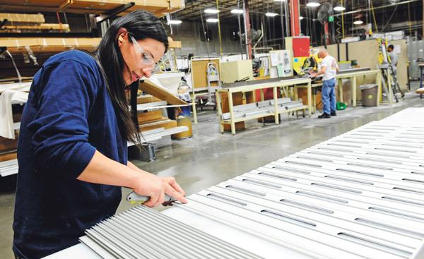 Kristin Ricketts assembles a roll-up door at R-O-M Corp. in Belton.