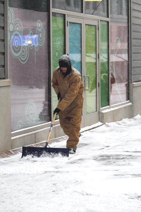 A worker shovels snow in the Kansas City Power & Light District.