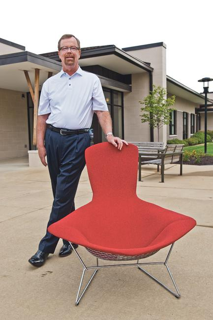 """Chris McCormack, CEO of Spaces Inc., leans on a Knoll Inc. """"Bird Chair"""" designed by Harry Bertoia."""