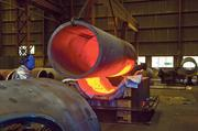 """A section of red-hot pipe is lifted from a kiln at the Taylor Forge plant. In the next step in an """"extrusion"""" process, an opening will be forced through the molten metal."""