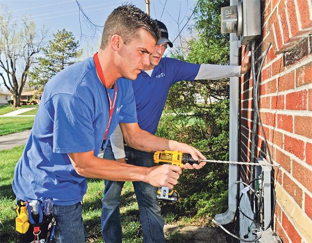 Barrett Watson (left) and Matt Long, installers for Time Warner Cable, bring high-speed cable to a Merriam home just south of Wyandotte County.