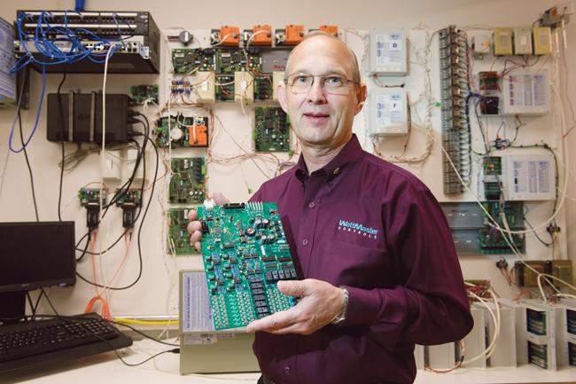 Michael Hobbs, owner of WattMaster Controls LLC, holds a temperature control unit that the company makes for industrial companies, large hotels and other high-end, nonresidential clients.