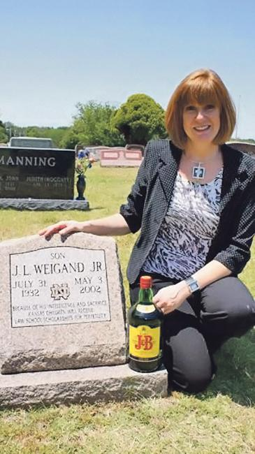 Claudette Glenn, director of The J.L. Weigand Jr. Notre Dame Legal Education Trust, kneels at Weigand's Wichita grave. Weigand enjoyed J&B scotch and Planters peanuts after his long days in the office.