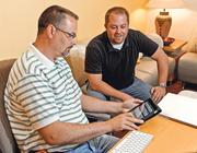 Jeff Garoutte (left), production manager of Propaganda3, and producer Dan Mingori look over information on Garoutte's iPad.