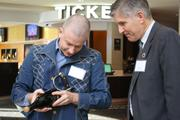 Richard Usher, assistant city manager, and Alamo founder Tim League try to find the seam of the champagne bottle — the target area for a perfect saber.