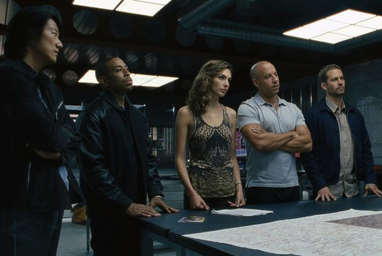 """A scene from """"Fast & Furious 6."""" Paul Walker is at far right. Vin Diesel is to his left."""