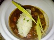 The third course is a black roux gumbo with rock shrimp dumpling and hominy.