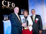 Business First publisher Tom Monahan, left, presents a CFO of the Year  award to Sharon Orman, of Hosparus Inc. Mark Stegeman, vice president and assistant treasurer of Brown-Forman Corp. and president of event sponsor the Louisville chapter of Financial Executives International, is pictured at right.