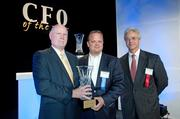 Business First publisher Tom Monahan, left, presents a CFO of the Year  award to Bill Mudd, of Churchill Downs Inc. Pictured at  right is Kendrick Riggs, of event sponsor Stoll Keenon Ogden.