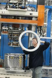 An employee adds a part to the interior basket of the new top loading washer at GE.