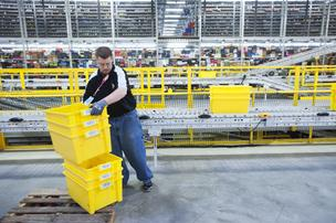 Mike Petree loaded a conveyor with empty bins for product at Amazon.com Inc.'s fulfillment center at River Ridge Commerce Center in Jeffersonville.