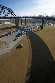 The walkway to the Big Four Bridge cast a shadow on The Great Lawn at Louisville Waterfront Park.