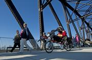 A rider on a recumbent bicycle shared the Big Four Bridge walkway with pedestrians.