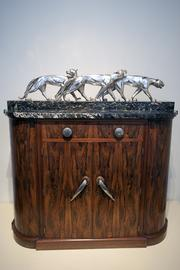 An Art Deco Cocktail Cabinet with Rosewood and Marble topped by a  silvered metal and marble prowling panthers sculpture is included in  the Bittners display at the Frazier History Museum.