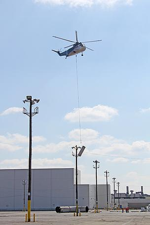 A helicopter removes duct work from the roof of the Louisville Assembly Plant.