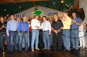 Texas Roadhouse CEO and chairman, who is wearing a cowboy hat, is shown at the company's grand opening at a restaurant in Dubai.
