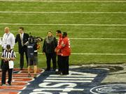 Boxing legend Muhammad Ali, in No. 5 jersey at right, U of L football legend and ESPN commentator Tom Jackson, in the No. 50 jersey, and Ali's wife Lonnie, were among the celebrities on the field before the Sugar Bowl.