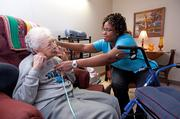 Te'Onna Davey, a certified nursing assistant for Chrisitan Care Communities, helped Margaret Pike adjust her breathing treatment apparatus. Pike is a resident of Christian Health Center, located at 920 S. Fourth St.
