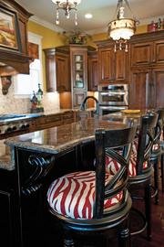 This kitchen includes decorative flairs such as the red zebra print seats on the chairs by the island.