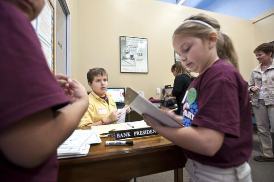 Holden Hooper assumed the role of bank president at the Junior Achievement BizTown in November 2011 when fifth graders from Jeffersontown Elementary School participated in the program. Alejandro Rojas, left, and Tori Haggard were assuming the roles of advertising executives with a radio station.