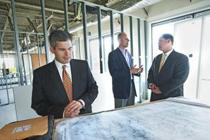 David Hardy, left, of CBRE/Louisville, looked over blueprints for space being converted in the Ormsby II office building for Jefferson National Financial Corp. In the background are Craig Hawley, general counsel and secretary for Jefferson National, left, and David Williams, the CBRE employee who brokered the deal.