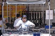 Delores Jackson works on an automotive part at the Faurecia Interior Systems plant in Eastpoint Business Center.