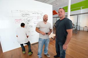 Mark Palmer, founder and chairman of Oohology, left, and Sean  Breslin, president, are shown in their office in front of a wall used as  a white board where ideas are drawn on the fly. Designer Tony Ostertag  was working on ideas for the Tony Boombozz pizza chain's Web site.