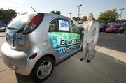 Dick Swope is shown with one of the Mitsubishi innovative Electric Vehicles (MiEV) on the lot at Sam Swope Auto Group.