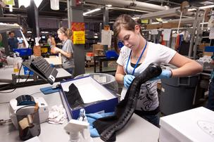 A Zappos employee checks the quality of a returned pair of boots.