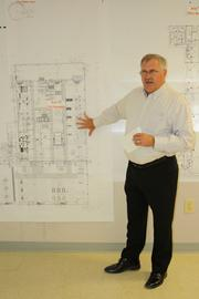 Ken Badaracco, general manager of Mitsubishi's Power Transformer Division, gives tour attendees a rundown of project blueprints and progress at the Mitsubishi Electric worksite. The project is estimated to be around 70 percent complete; Badaracco said the build is on schedule and he expects production to begin April 1, 2013.