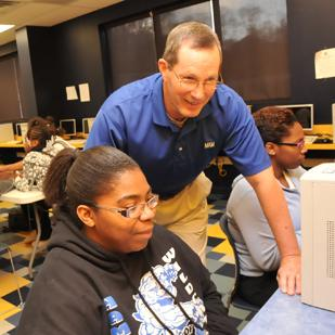 Gib Vestal, chief executive officer of Memphis Athletic Ministries, assists student Rozaland Wright in financial literacy program.