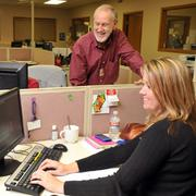 Mike Hopper, chief financial officer of Memphis-based Ozark Motor Lines Inc., watches Averi Chism help a customer online from Ozark's offices.
