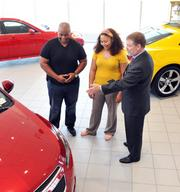 Henry Hutton in Chuck Hutton Auto Group showroom with Lamaar and Ka'ren Chatman