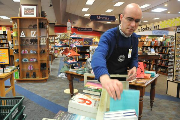 Ivan Esteves checks a display at The Booksellers at Laurelwood. Brick-and-mortar book retailers are in decline.