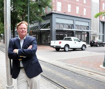 Mike Ratliff says Center City incentives were 'critical' in APG Office Furnishing's decision to open a space in Barboro Flats development, pictured in background.
